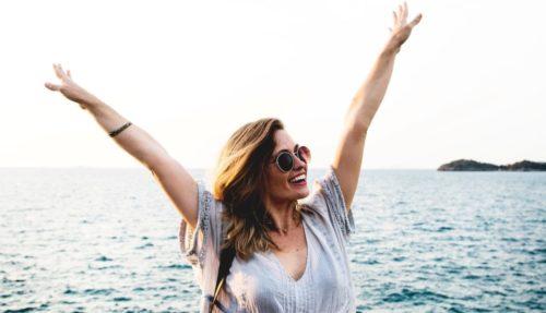 Une femme radieuse portant des lunettes de soleil lèvent ses bras pour signifier son bonheur